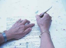 A person (only hands visible) writing a ketubah